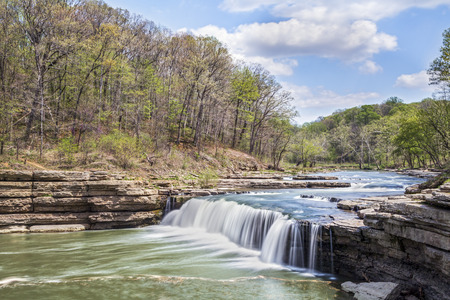 cataract falls: Whitewater flows over Indianas Lower Cataract Falls under a cloudy blue spring sky. Stock Photo
