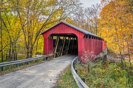 Putnam County, Indiana's Pine Bluff Covered Bridge crosses Big Walnut Creek in an autumn landscape.