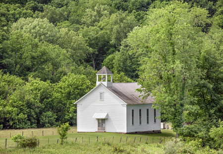 wildwood: A small white church building is backed by a hillside full of green trees in rural Monroe County, Ohio.