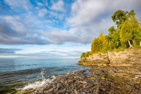 stoney point: A small wave breaks and splashes under a cloudy blue sky at Door County, Wisconsins Cave Point on the coast of Lake Michigan.