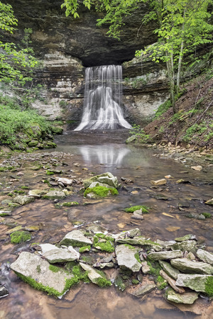 immediately: Water flows from Porter Cave and immediately tumbles over a steep waterfall in rural Indiana.