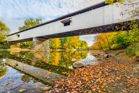 west river: Potters Covered Bridge crosses the West Fork of the White River surrounded by colorful fall foliage in Noblesville, Indiana.