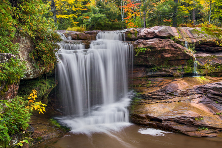 plunging: O Kun de Kun Falls, a plunging waterfall in Michigans western Upper Peninsula, pours over a rocky cliff surrounded by autumn foliage.