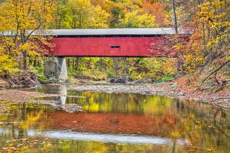 pine creek: Autumn foliage surrounds Pine Bluff Covered Bridge reflected in the waters of Putnam County, Indianas Big Walnut Creek.