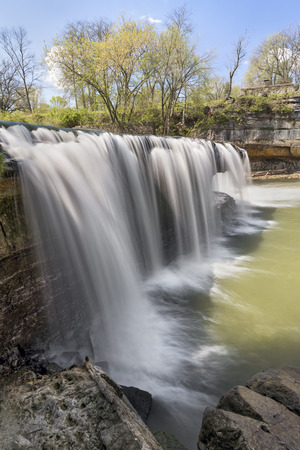 cataract falls: Mill Creek plunges over Upper Cataract Falls, a waterfall in Owen County, Indiana, under a cloudy blue spring sky. Stock Photo