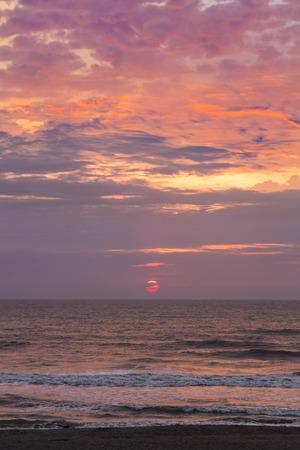 cocoa beach: The sun rises over the Atlantic Ocean with moody pastel tones on a Florida beach.
