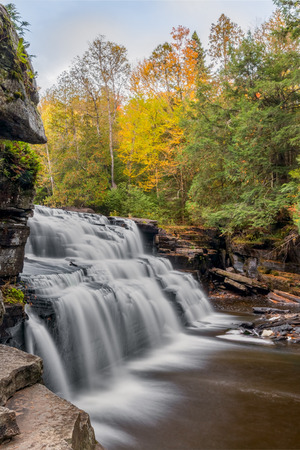 whitewater: Whitewater cascades over rocky ledges with autumn trees at Canyon Falls, a beautiful waterfall in Upper Peninsula Michigans Baraga County.