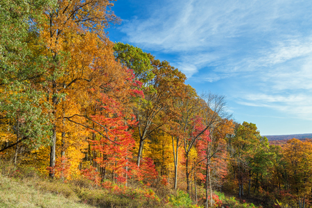 hillsides: Trees display colorful autumn foliage on hillsides under a cloudy blue sky in Brown County, Indiana.