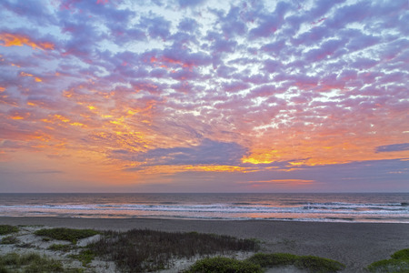 cocoa beach: A cloudy and colorful pastel sky is reflected on the Atlantic Ocean with gently breaking waves on a Florida beach.
