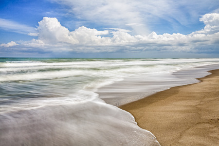 cocoa beach: Waves breaking gently on a sandy beach with a cloudy blue sky above are captured with a longer exposure, showing motion in the surf.