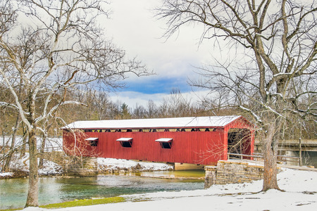 covered in snow: Framed by huge sycamore trees and topped with snow, Indianas red Cataract Covered Bridge spans Mill Creek in Owen County.