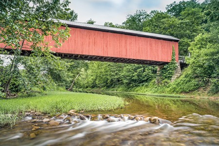 of yesteryear: Ohios historic red Hune Covered Bridge is viewed from the Little Muskingum River below.