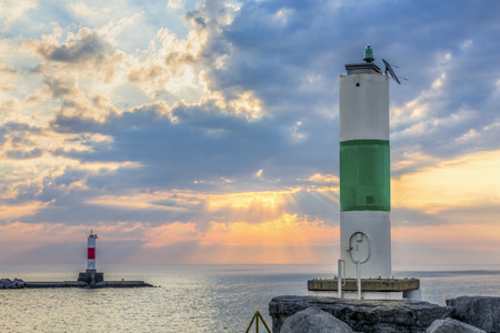 beacons: Harbor beacons on breakwaters are backed by a glorious morning sky over Lake Michigan at Kenosha, Wisconsin.