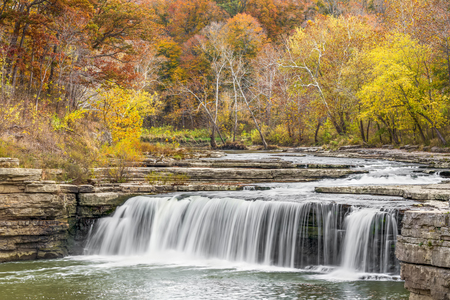 Lower Cataract Falls, a wide waterfall in Owen County, Indiana, is surrounded by beautiful fall foliage.