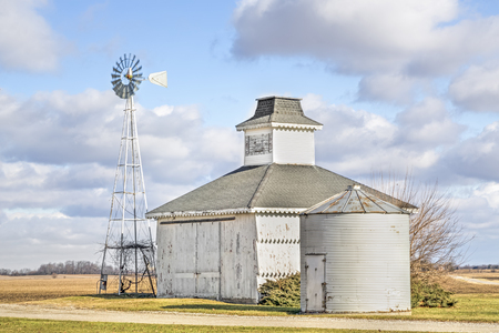 A small white barn and windmill stand under a cloudy blue Midwestern Sky.