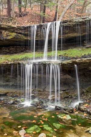 Water splashes down the two tiers of the waterfall at Oglebay Park in Wheeling, West Virginia with autumn leaves here and there. Stock Photo