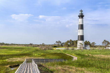 hatteras: A board walk leads the eye to the historic Bodie Island Lighthouse at Cape Hatteras National Seashore on the Outer Banks of North Carolina. Stock Photo
