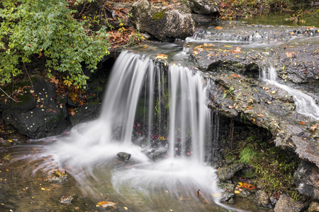 A small waterfall plunges over a rocky ledge in Englewood, Ohio.