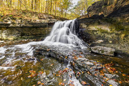 Whitewater cascades through an autumn landscape at McCormicks Creek Falls, a waterfall in rural Owen County, Indiana.