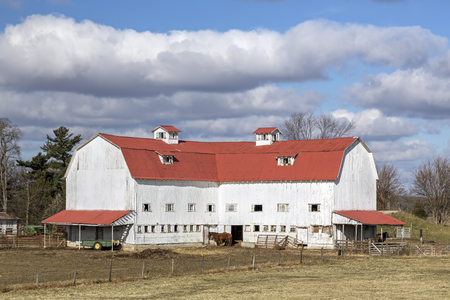 A large white barn with red roof and horses stands under a cloudy blue sky in Midwestern America.
