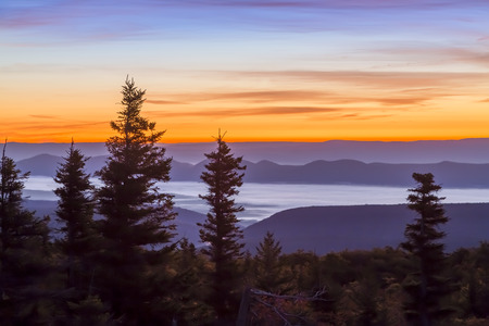 Sunrise paints the morning sky and mountain landscape over the Allegheny Front as viewed from Bear Rocks at the Dolly Sods Wilderness of West Virginia. Stock Photo