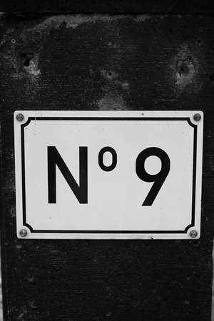 cypher: House number 9 Black cypher on white fascia secured on old wall. black and white image.