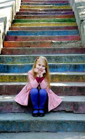 litle: Beautiful blonde litle girl sit on the multi-colored steps