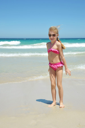 Little happy blond caucasian girl child in pink swimwear playing in the sean and having great holiday fun. Standard-Bild