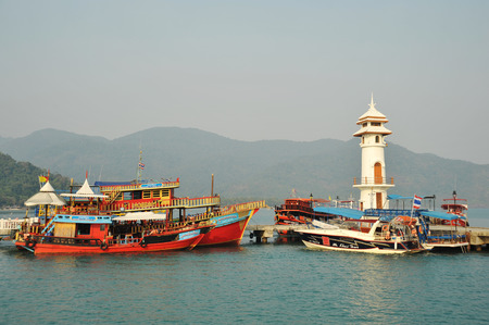 trad: Pier with lighthouse and fishing boat at Koh Chang Trad Thailand Stock Photo
