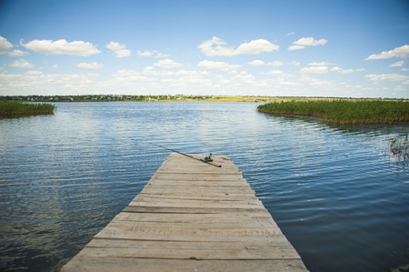 Lonely fishing rod on old wooden pier on the lake