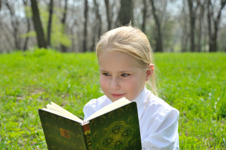 Adorable cute little girl reading book sitting outside on grass