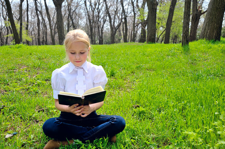 little blond girl reading book between green spikes meadow garden photo