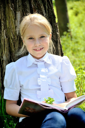 Cute little girl in a white blouse sitting in the grass near a tree in the countryside with book Stock Photo