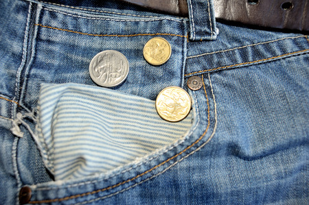 empty pocket: Old jeans and australian dollars coins near empty pocket