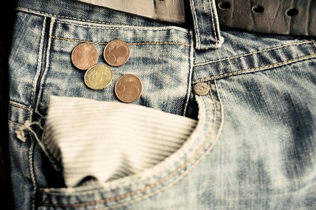 empty pocket: Old faded jeans with euro coins near empty pocket