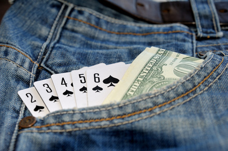 Play card Straight Flush and money in the blue jean pocket.
