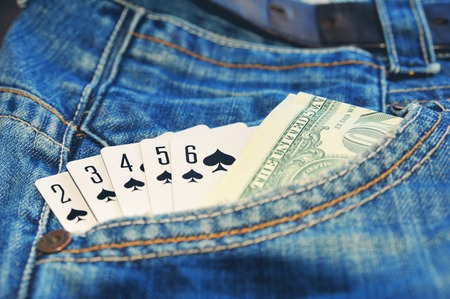straight flush: Play card Straight Flush and money in the blue jean pocket.