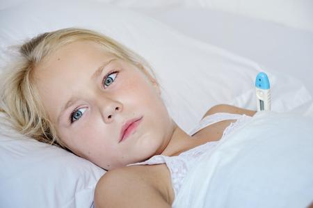 ni�os enfermos: Ni�a linda con un term�metro enfermo acostado en la cama