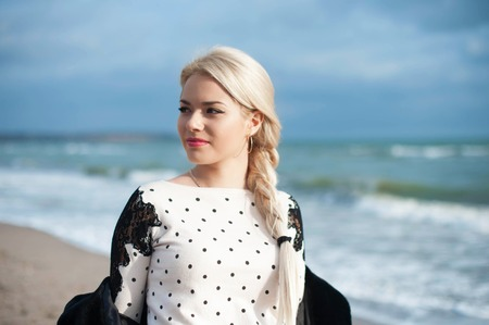 feeling good: Portrait of the beautiful blonde woman at the  autumn day relaxing on coast feeling good
