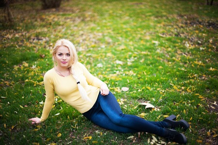 Portrait of beautiful young woman which sits on green grass on natural background