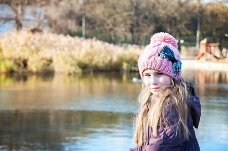 sweater girl: Little beautiful blonde girl in pink hat on background of autumnal lake looking at camera Stock Photo