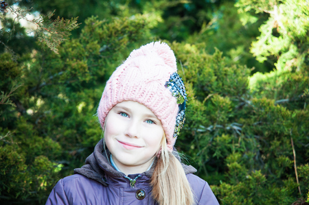 colegiala: Close up portrait of a cute little girl in winter time with spruce on background