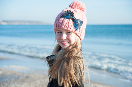 Portrait of 8 years old girl  near sea in pink hat, still life photo Stock Photo
