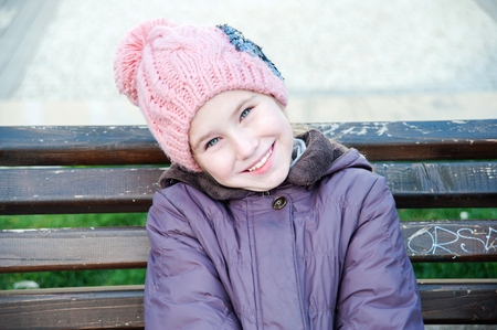 pink hat: Happy girl-schooler sitting on bench in pink hat in city park.