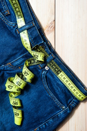 loosing: Jeans and a measuring tape.Concept of loosing weight.