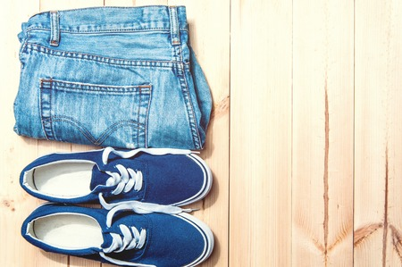 scuffed: Youth blue sneakers  and blue jeans with scuffed on wooden background with copy spase Stock Photo