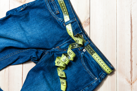 decreasing in size: jeans and centimeter on a wooden background close up