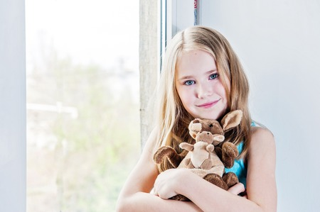 8 years old: beautiful girl 8 years old playing with her toy big and little kangaroos near window
