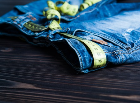 centimeter: jeans and centimeter on a wooden background close up