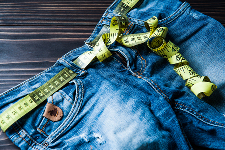 jeans and centimeter on a wooden background. clothing Stock Photo